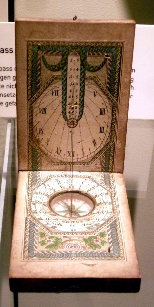 Eine Taschensonnenuhr, aufgeklappt. Die Taschensonnenuhr ist Handbemalt. Sie besteht aus zwei rechteckiegen Elfenbeinklappen, die aufgeklappt sind wie ein Kalender. Auf der unteren Hälfte ist ein Kompass angebracht-