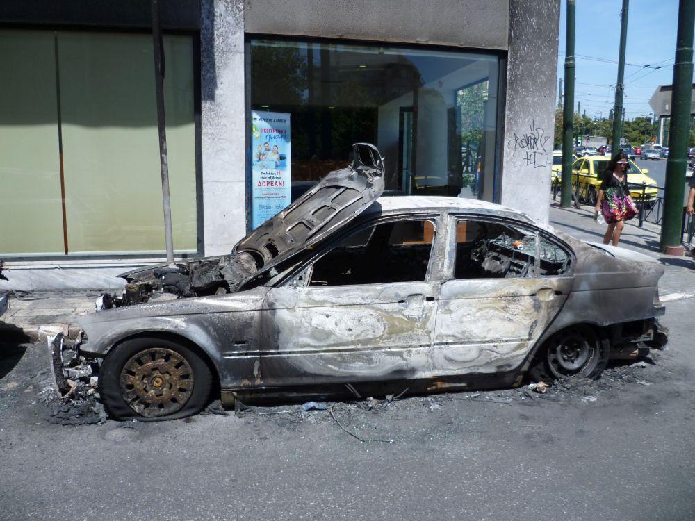 Ein Ausgebranntes Auto vor einem leer stehenden Ladengeschäft