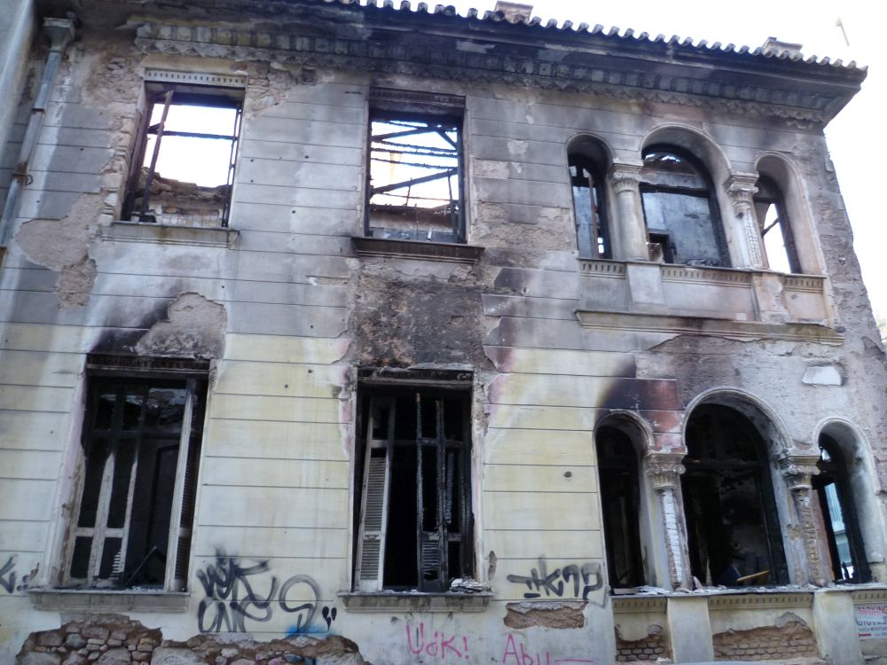 Ein Ausgebranntes Haus ohne Dach. Das Haus hat keine Fenster und gerde im Erdgeschoss ist viel Ruß zu erkennen.