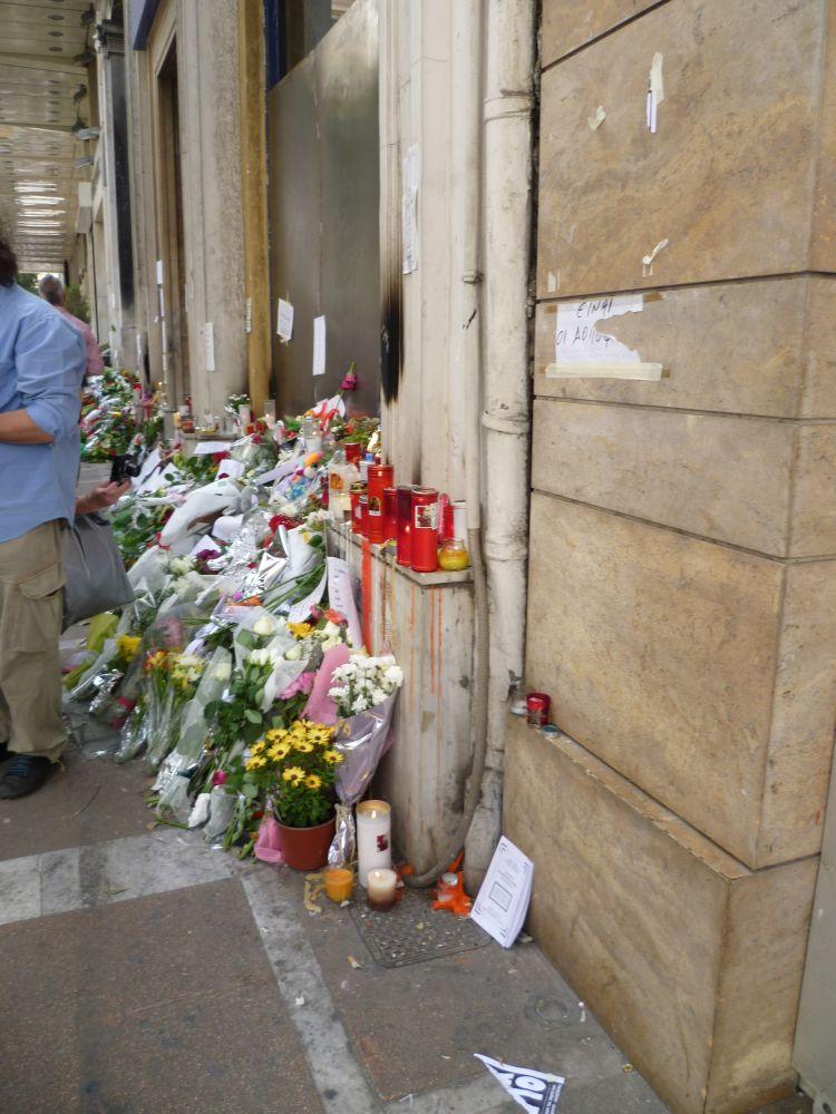 Ein abgesperrtes Gebäude davor liegen hunderte Blumen, rote Trauerkerzen. Auch ein paar Briefe sind zu sehen.