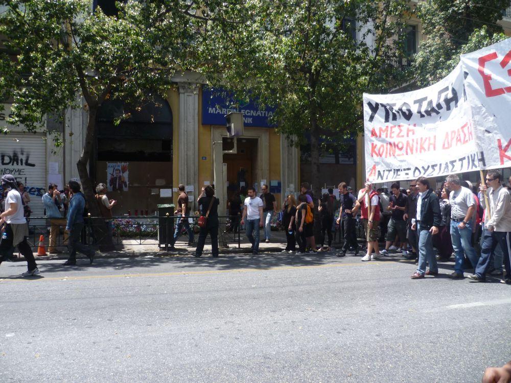 Eine Demonstration. Einige Leute Tragen ein Transparent über den Köpfen. Sie stehen vor der Ausgebrannten Bank.