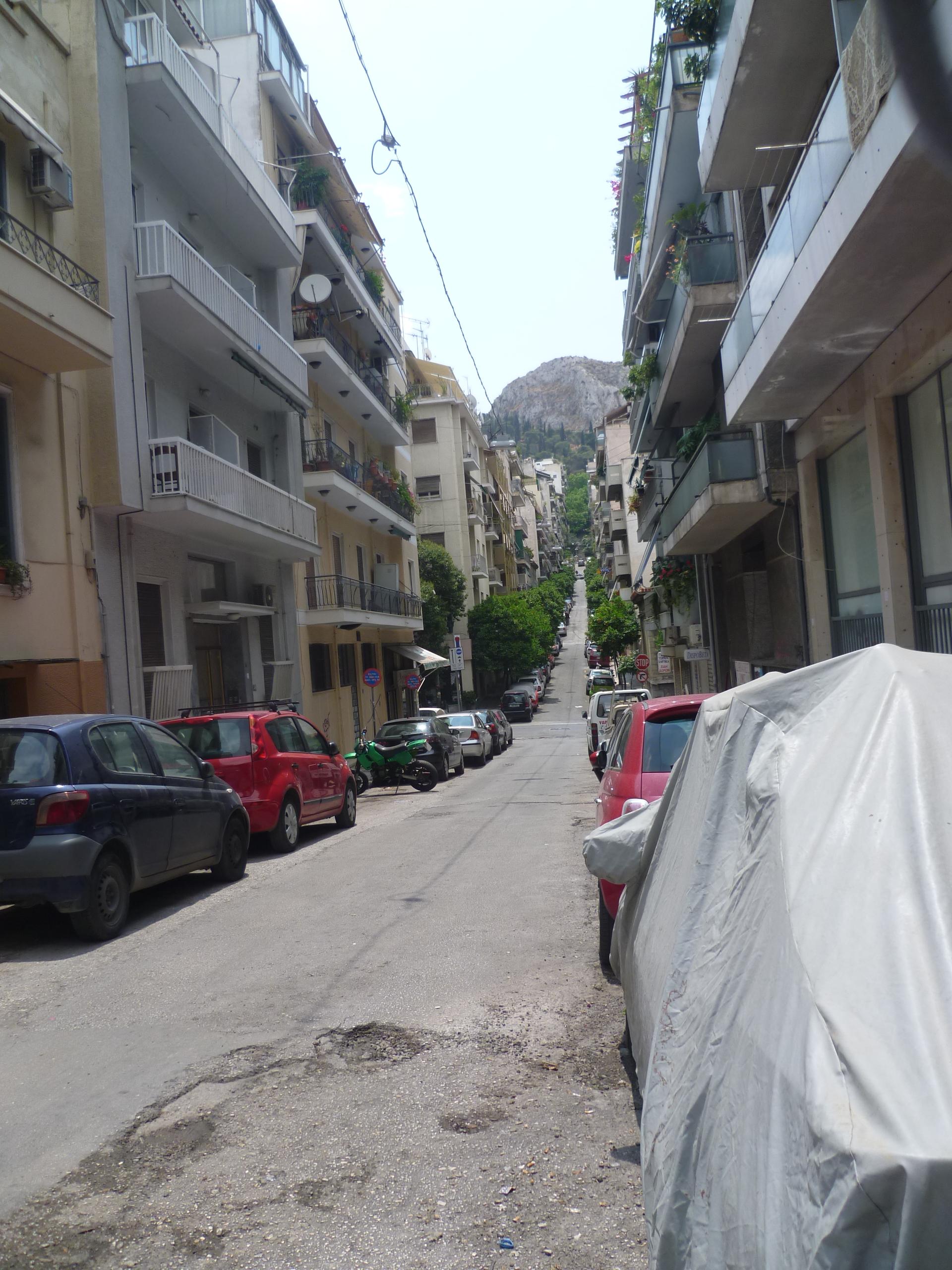 Eine Strasse die durch Athen einen Berg hoch führt. Sie ist Kilometerweit einzusehen. Links und rechts parken Autos. Kein Mensch ist zu sehen.