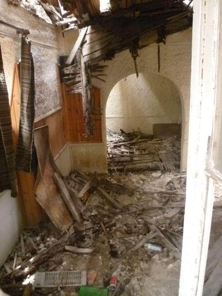 Der Innenraum eines Hauses. Das Dach ist eingebrochen, das Haus liegt Knieehoch mit Schutt. Dennoch hängen Gardinen im Fenster.