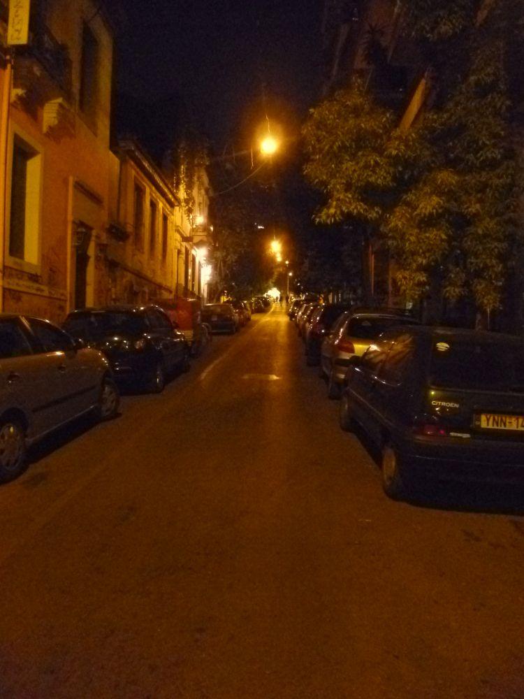 Eine Einbahnstrasse, links und rechts parken Autos. Erhellt wird die Strasse durch orangene Lampen.