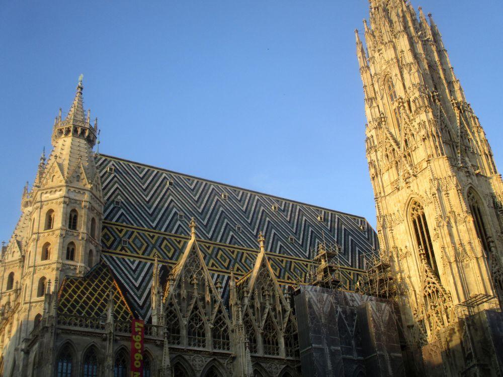 Dach und Teil des Turmes vom Stephansdom. Das Dach ist mit Bunten schindeln im Zickzackmuster gedeckt.