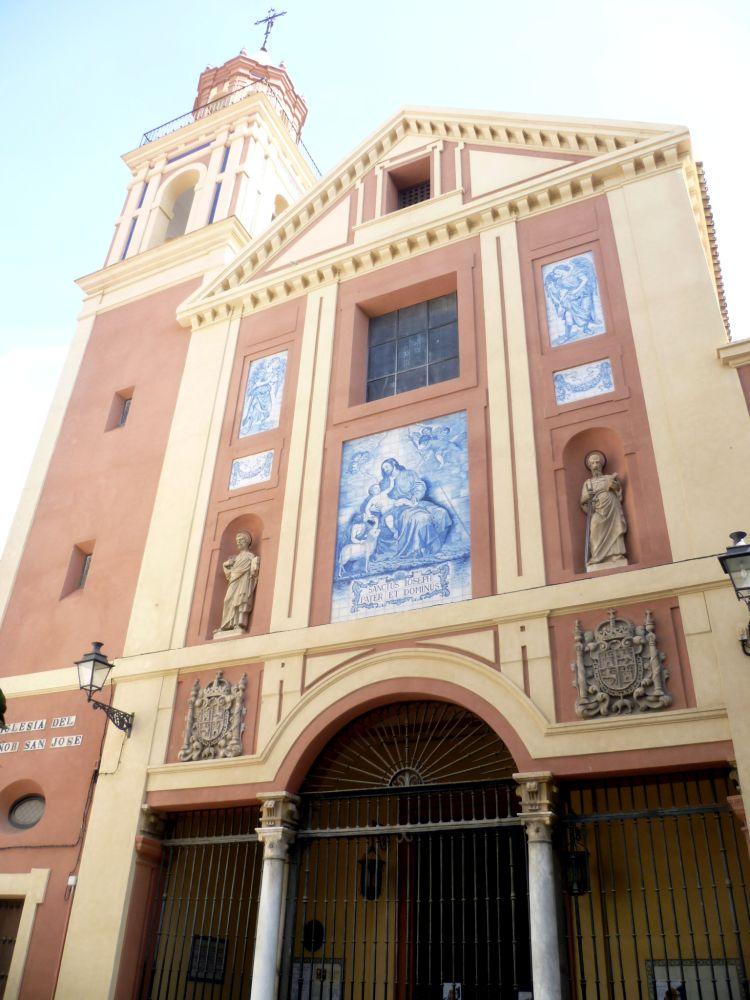 Ein Rosa Kirchenbau mit einem Schiff und einem nebenstehenden Turm. Eineige Heiligenbilder aus blau bemalten Kacheln sind an der Aussenfassade angebracht.
