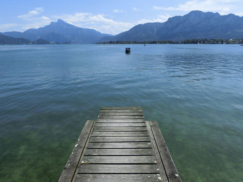 Mondsee, Im Hintergrund sind die alpen, im Vordergurnd Grünblaues Wasser und ein Bootssteeg aus Holz.