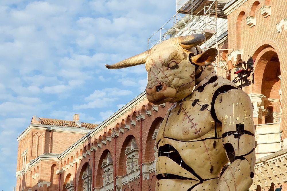 Eine Riesenmarionette, der Le gardien du temple, in form eines Minotaurus steht in Toulouse vor einem Roten backsteinhaus. Der Wächter ist so groß, das er in die oberen Stockwerke blicken kann.