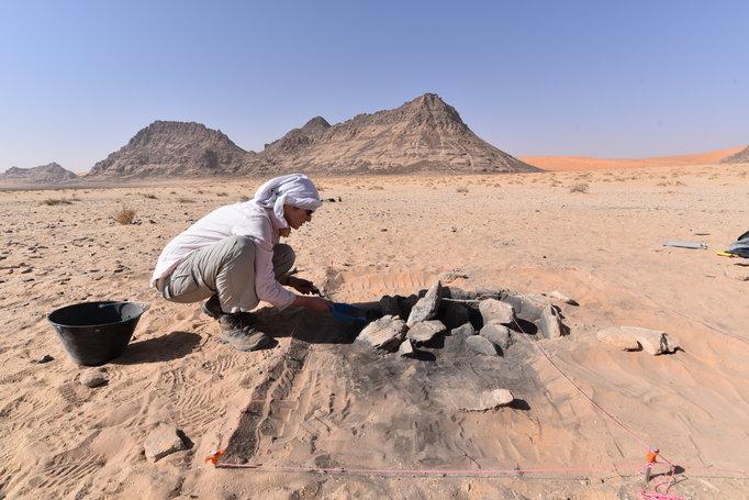 Eine Archäologin in weiser Kleidung mit einem weisen Turban kniet vor einer Feuerstelle im roten Wüstensand.