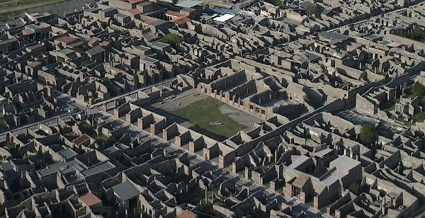 Die Ruinenstadt Pompeij von oben fotografiert. In der mitte der Hausruienen ist ein grüner platz.