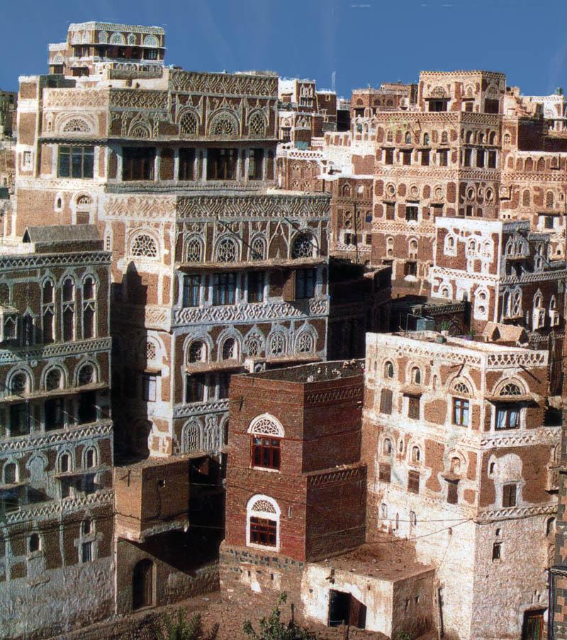 Die Wohntürme von Sanaa. Es handelt sich um Lahmbauten die mit weisen Kalkmustern verziert sind. Die Hochhäuser der Wüstenstadt reichen in den blauen Himmel hinauf.