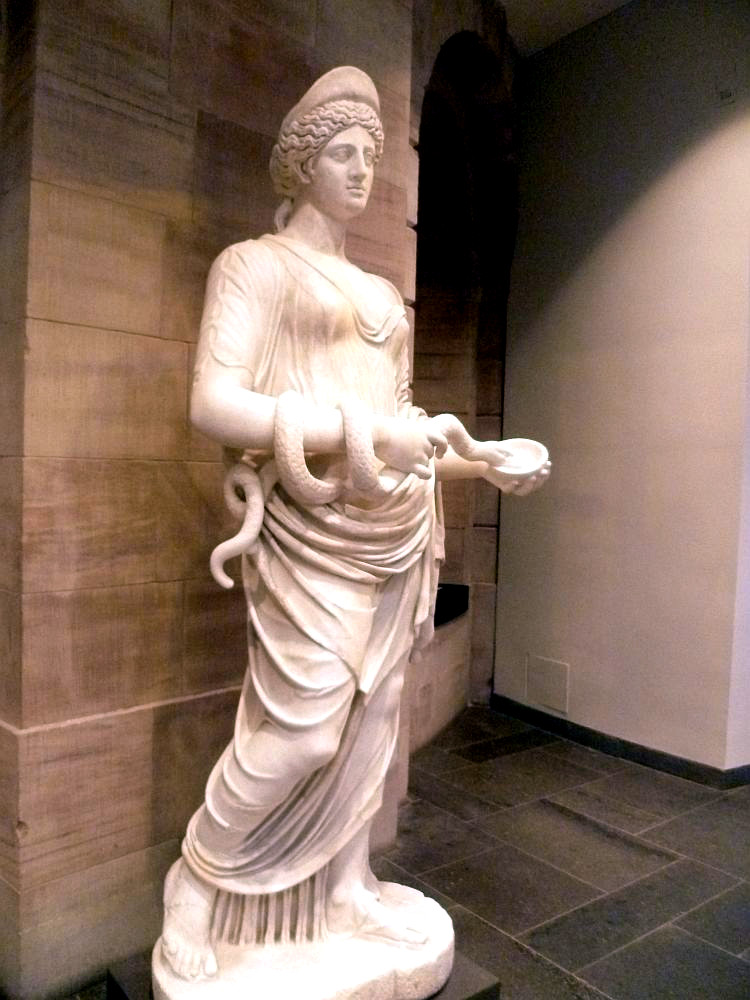 Eine weise Marmorfigur. Sie ist Überlebensgroß, und zeigt Hygieia. Die Figur trägt eine Haube auf einer zusammengerafften Lockenfrisur und ein Naheezu durchsichtiges Gewand. Um den Rechten Arm ist eine Schlage gewickelt, die die Frau mit einer Schale in der anderen Hand füttert.