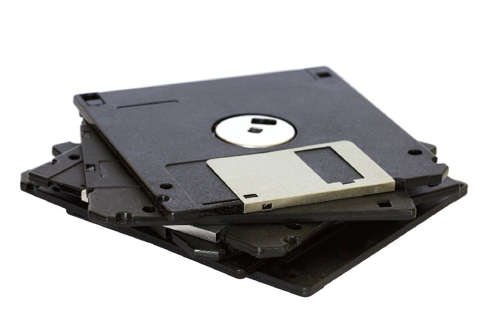 Ein Bild mit drei aufeinandergestapelten schwarzen Disketten vor einem weißen Hintergrund.