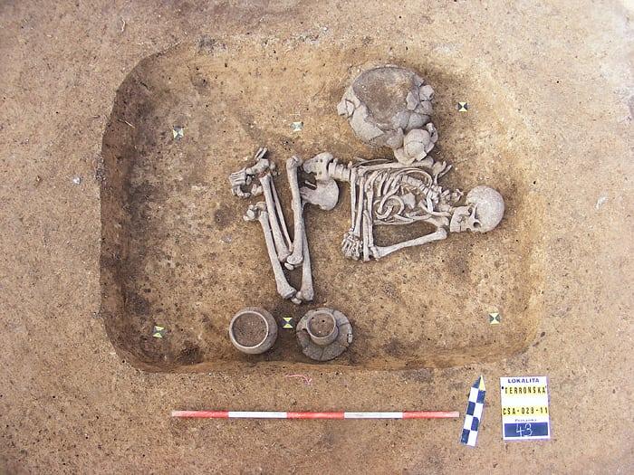Eine Besattung. Ein Skelett ist zu sehen, das in einer Grube leigt. Es hat im rchten Winkel angewinkelte Oberschenkel, und liegt auf der linken Körperhälfte. Einige Keramikgefässe wurden dr Bestattung beigelegt.