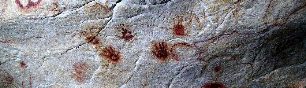 Rote Handabdrücke aus der Grotte Chauvtte. es handelt sich um 6 Altsteinzeitliche Handabdrücke aus roter Farbe, di auf einen Grauen Stein gemacht wurden.