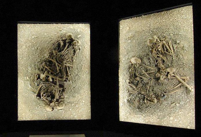 Ein Bild mit zwei Gemeinschftbestattungen. In einer Bestattung sind die Knochen von 4 aneinandergekuschelten Menschen zu sehen, in dem anderen kuschelt sich ein Kinderskelett an ein erwachsenens.