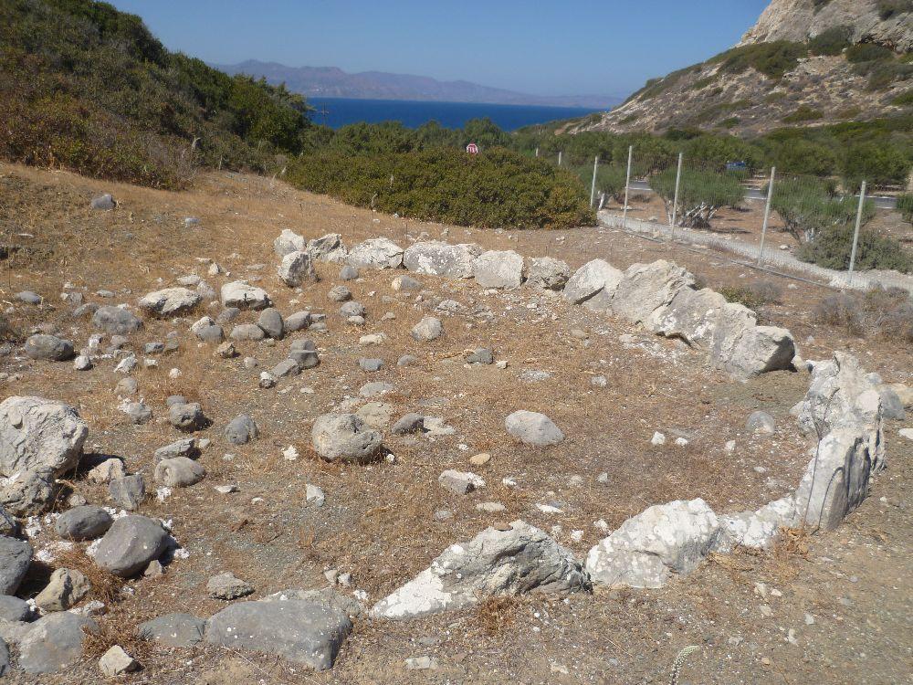 Viele Steine liegen auf einem Roten Erdboden, sie sind von einer leicht ovalen Steinstuktur umgeben.