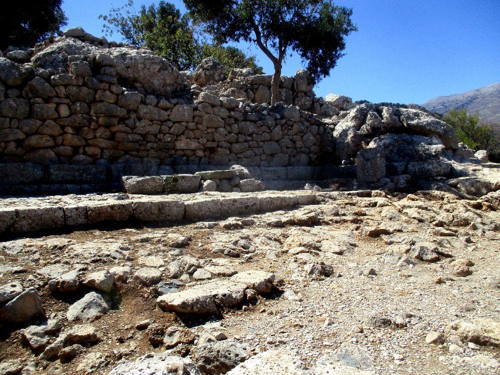 Eine lang Steinstufe vor einer alten Mauer, davor erstreckt sich ein Platz.
