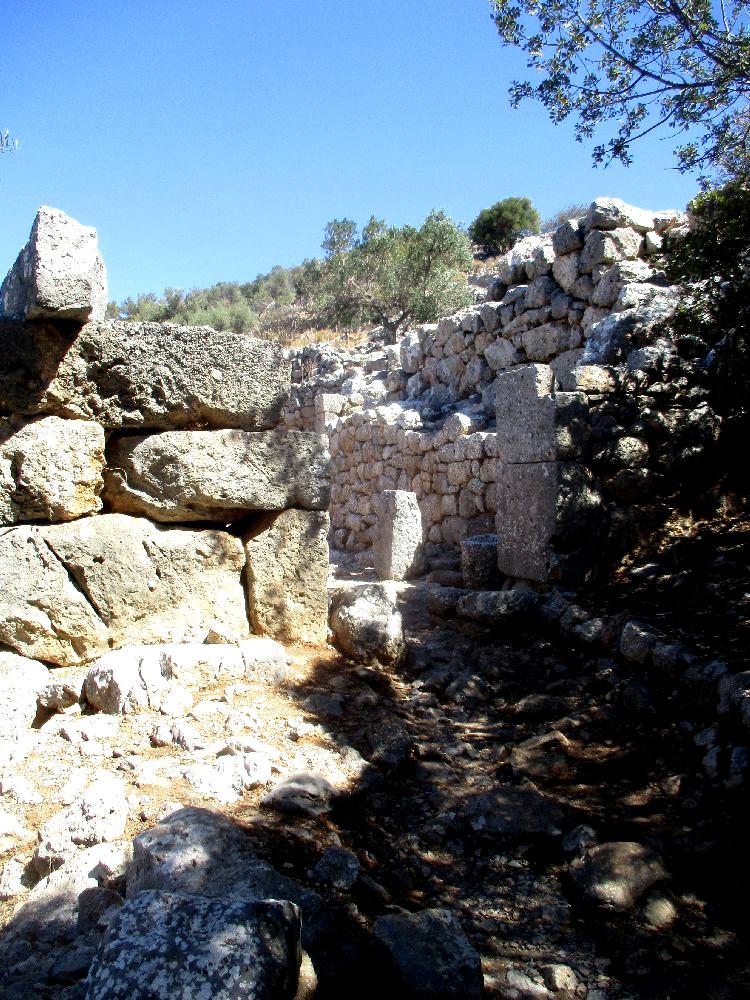 Der Eingang zu der archäologischen Siedlung Lato auf Kreta. Im vordergrund ist eine Massive Festungsmauer zu sehen, mit einem schmalen durchgang von weniger als einem Meter breite. Dahinter erstrecken sich ein paar rester einer Architektur die aus filigraneren helleren Steinen gebaut ist.