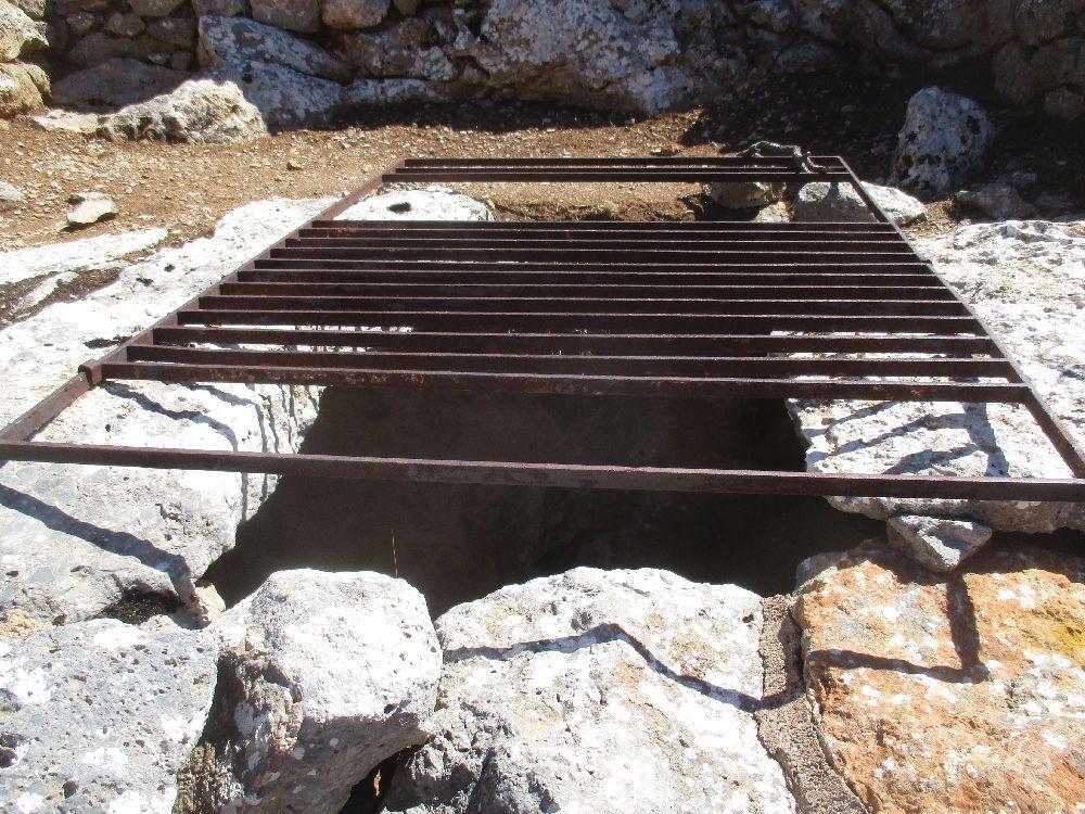 Ein Kaputte Gitter über einem Loch im Boden.