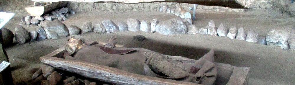 Ein geöffneter Baumsarg in dem eine Puppe liegt, die einen besttteten Mann darstellt. Er ist in ein Tuch eingewickelt, dass grau ist.