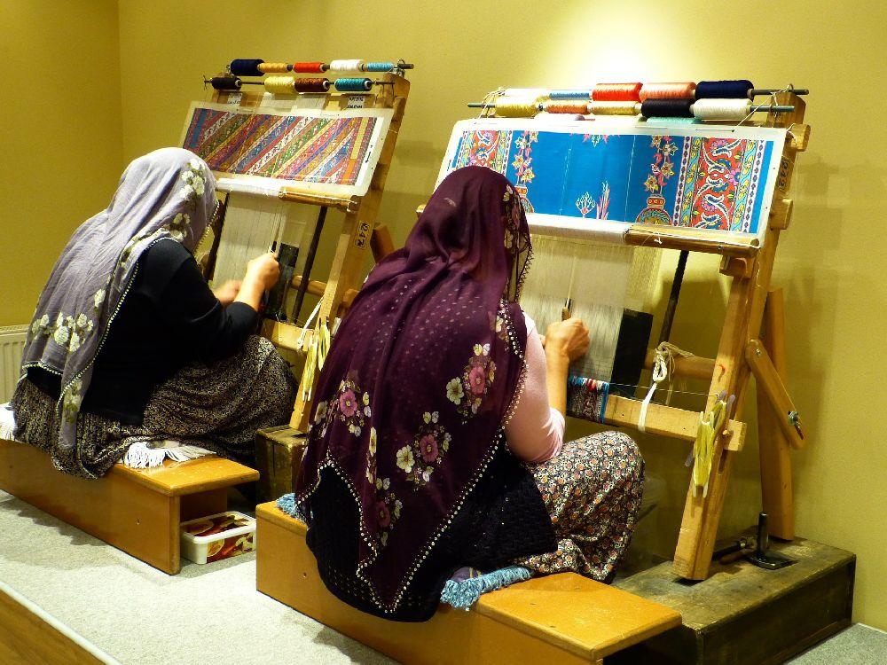 Zwei Frauen weben und knüpfen Teppiche. Die Frauen sind nur von hinten vor ihren Webstühlen zu sehen. Sie tragen Kopftücher.