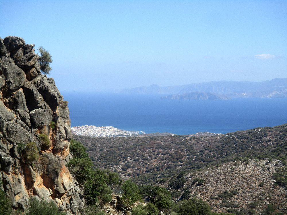Die Aussicht von einem Berg aus. Links sind noch ein Paar Felsen zu sehen, im Vordergrund ersteckt sich eine Landschaft. Eine Stadt, die aus weißen Häusern gebaut ist zieht sich ins Meer, das sich dahinter weithin sichtbar ausbreitet, und ganz im hintergrund ist noch ine Bergkette zu erkennen, von der anderen Seite der Meeresbucht.