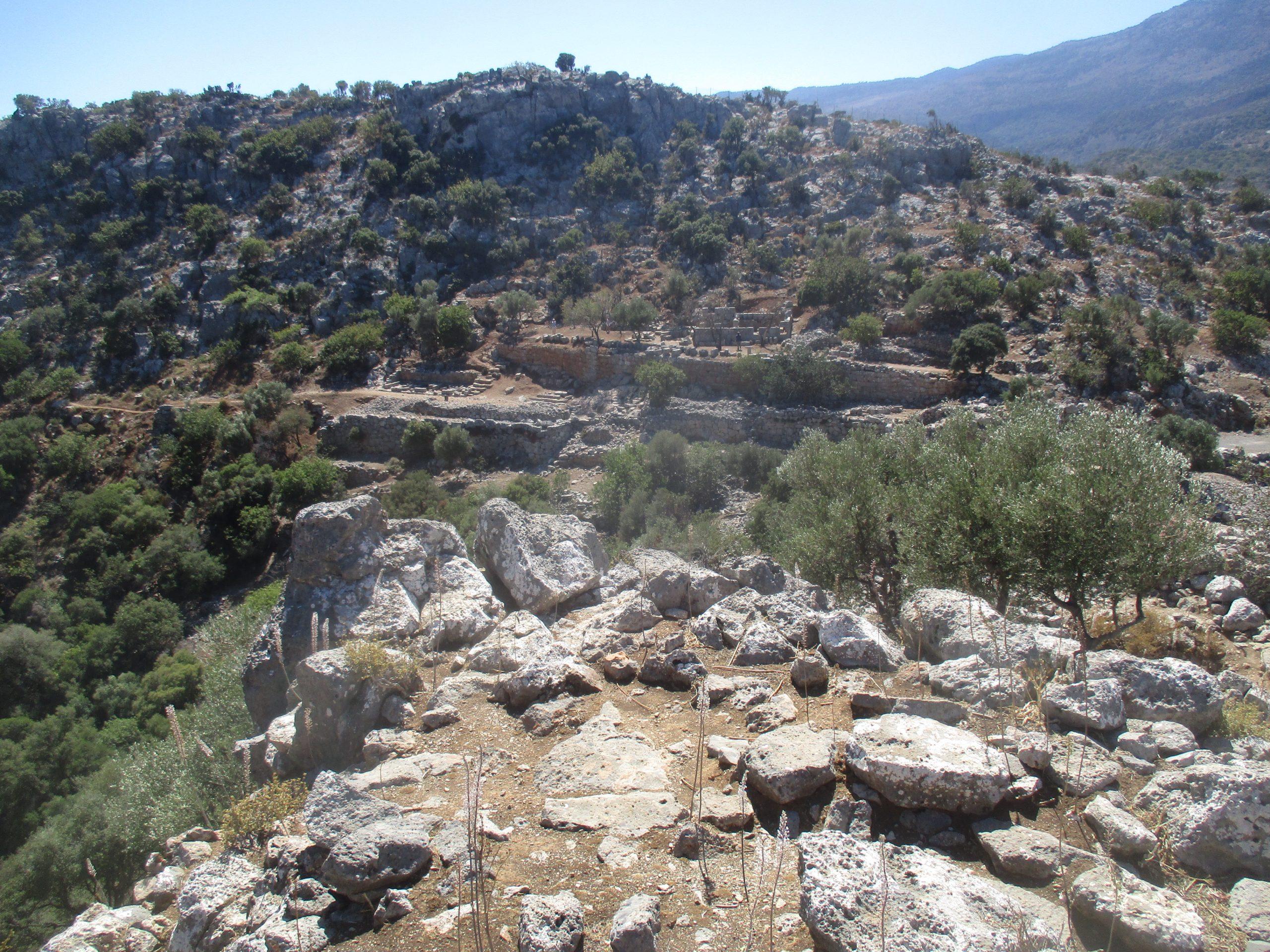 Der Blick vom westlichen Siedlungshügl der archäologischen Fundstätte Lato zum Östlichen Siedlungshügel. Zu sehen ist, das die Siedlung in Terrassen den Berg hochklettert. Es sind nur Ruienen von Häusern vorhanden.