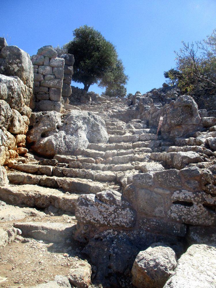 Eine Treppe aus groben Stein zieht sich einen Berg hoch. Sie verläuft eng zwischen Ruinen, ebenfalls aus weisen Steinen, die Grob behauen sind.