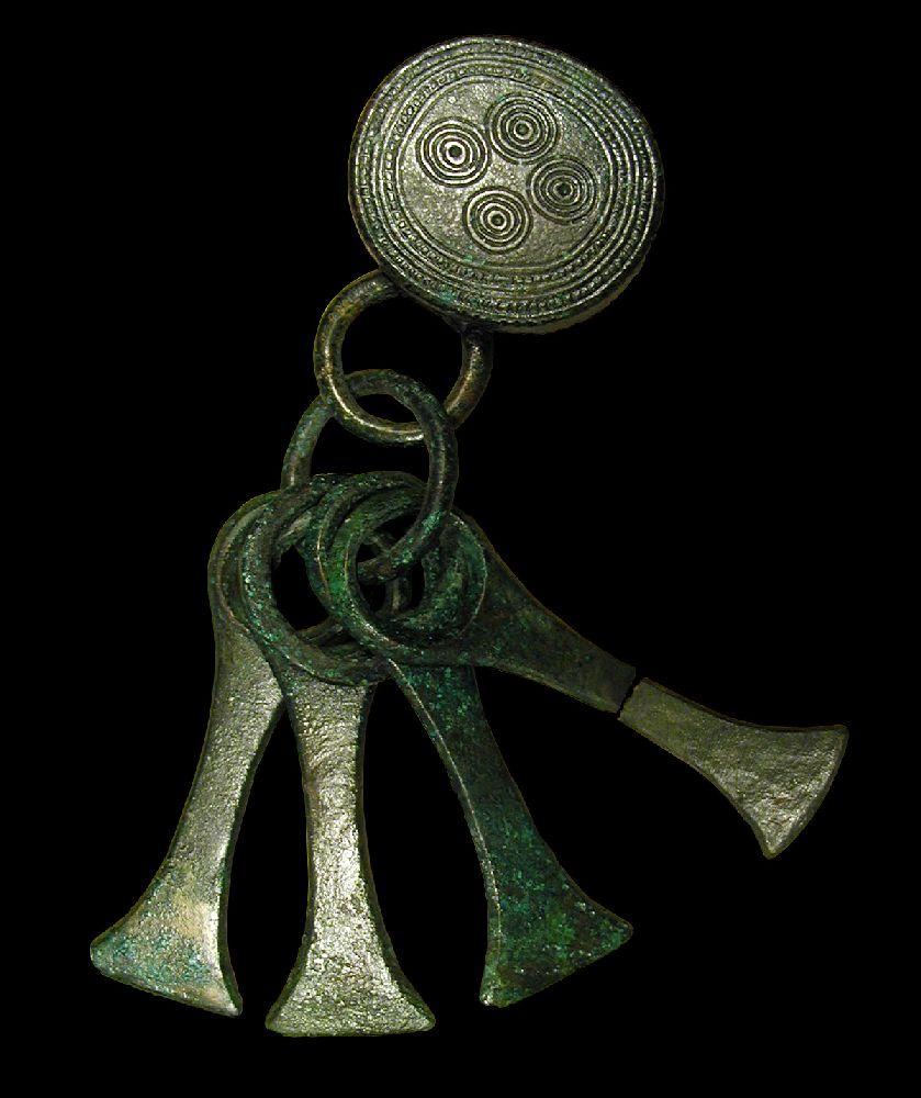 Ein rundes Beschlagblech, dass mit spiralen verziert ist, und an dem vier Anhänger hängen. Alles besteht aus Bronze.