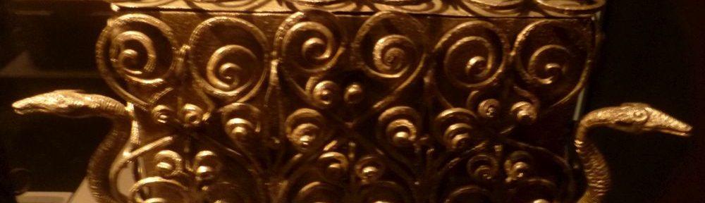 Ein Kästchen aus Eisen, das mit ganz vielen Spiralen auf Mtall verzihrt ist. Das Kästchen steht auf Füßen, die wi tierpfoten geformt sind, und links und rchts sind die Köpfe von Tieren, villeicht Enten ausgformt si das Kästchen zu tragen scheinen.