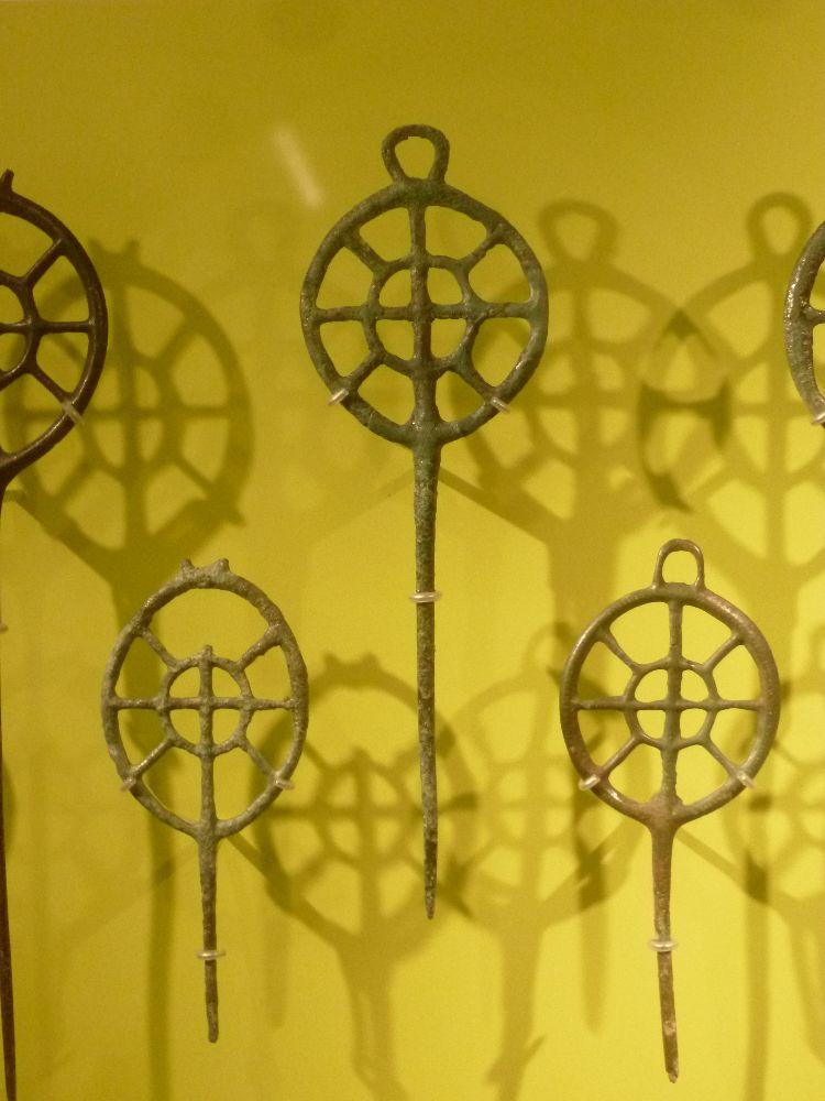 Einige Radnadeln vor einem gelben Hintergrund. Es handelt sich um Radnadeln mit einer öse über dem Rad. Das Rad selber hat inndn vier Speichen, ein Rad in der Mitt und drum herum ein weiteres Rad, das mit 8 Speichen befestigt ist.