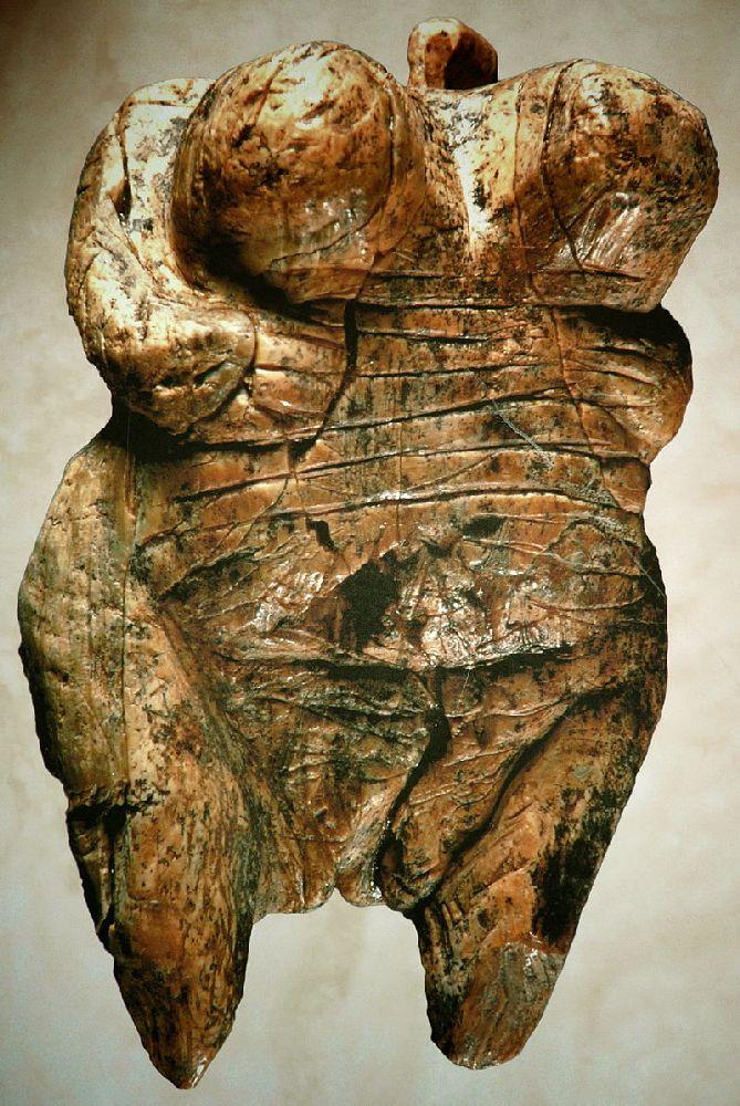 Eine Abbildung der Venus von Hohle Fels. Es handelt sich um eine Figur mit einem winzigen Kopf, und einem riesiegen Körper. Die Fru hält die Arme unter den Brüsten, die äusserst groß sind. Wie ist Korpulent und Nackt sodas ihre Vulva zu erkennen ist.