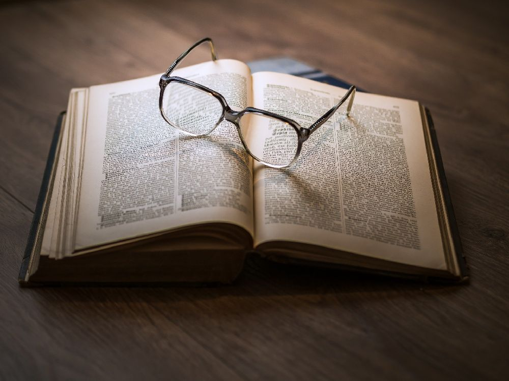 Eine Brille Liegt auf einem dicken aufgeschlagenen Buch.