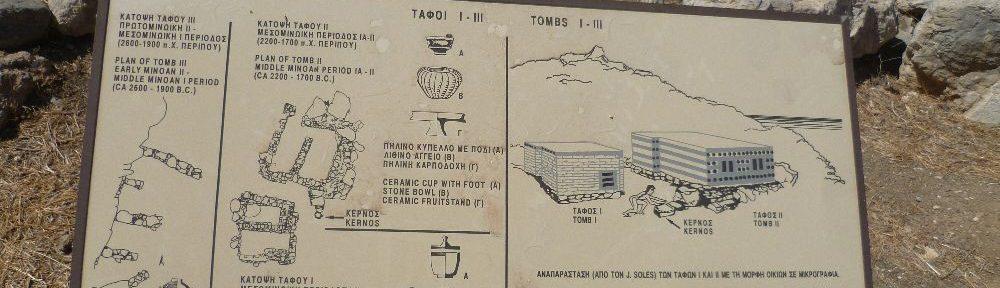 Ein Schild aus der archäologischen Stätte Gournia aus Kreta. Es sind die Rekonstrutionen zweier Grabhäuser dargstellt.