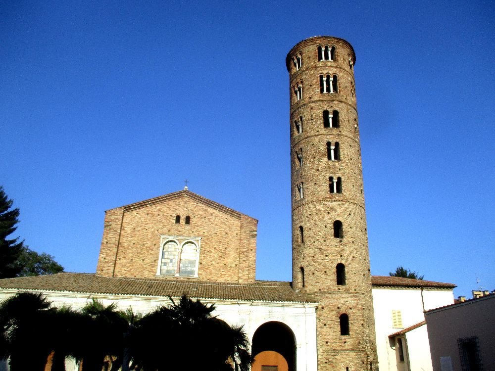 Die Saint Apollinare Nuovo von Vorne. Ein Bau aus rotbraunen Ziegeln ist zu sehen. Ein Runder Turm mit Bogenfenstern, und ein geziegeltes Kirchenschiff ist zu sehen. Dem Vorgelagert ist ein Bobengang aus einer jüngeren Zeit, der ein Teil der Architektur verdeckt.