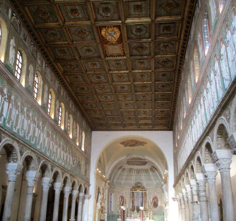Der Innenraum der San Appolinare Nuovo. Die Mosaike befinden sich Link und Rechts ber den Säulen eines Kirchenschiffes.
