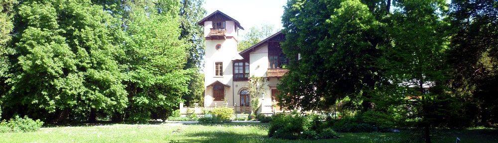 Das Casino am Starnbrger See. Eine Villa auf einer Wiese hinter Bäumen.
