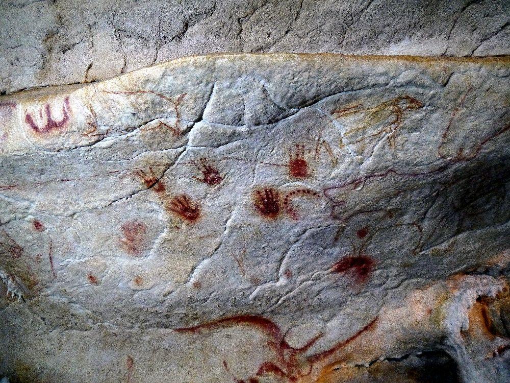 Eine Wand aus der Grotte Cauvette. Viele Handabdrücke die mit Roter Farbe gemacht wurden sind dabei zu sehen.