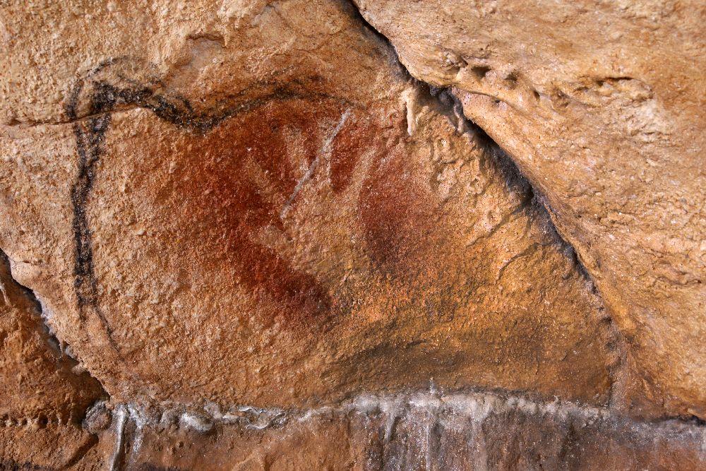 Ein Negativbild einr Hand. Die Hand wurde ggen den Fels gehalten, und dann rote Farbe aufgesprüht. Das geschah im Paläolothikum durch Spucken.