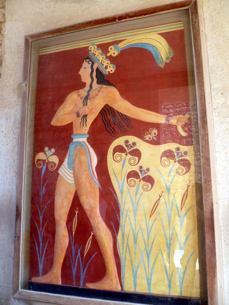 Der Lilienprinz aus Knossos. Ein Mann mit heller Haut und langen schwarzen lockieen Haar. Der Mann staeht vor einem roten Hintergrund offenbar in einem Lilienfeld. Er trägt eine blaugelbe Federkrone und einen blau weißen Lendenschurz.