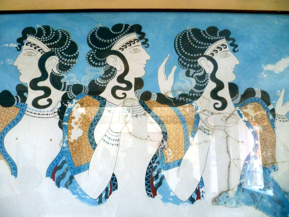 Die minoische Wandmalerier der dri weissen Frauen aus Knossos. Drei Fraun stehn nbneinandr, Sie tragen kurze Orangeblaue Jäckchen, die den Blick auf ihre nacktn Brüste freigeben. Die Frauen stehn vor einem blauen hintergrund, und sie tragn eine lange, mit perln verzierte Lockenfrisur.