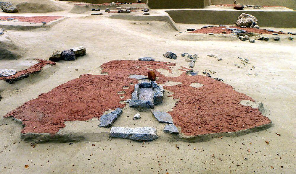 Ein Hausgrundgriss aus Lepenski Vir. Der Boden ist mit rotem Stein verfüllt. in der mitt befindet sich eine Herdstelle. Das Haus ist trapezförmieg. Die Breitere Seite des Trapezes zeigt nach Vorne.
