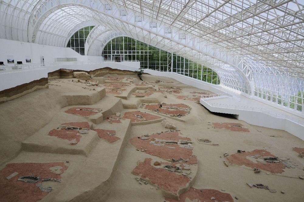 Die Hausgrundrisse von Lepnski Vir. Die Ausgrabungsstätte ist von einm Glasdach geschützt. Am Boden zeichnen sich haufenweise Hausgrundrisse ab. Sie haben einen roten Boden.