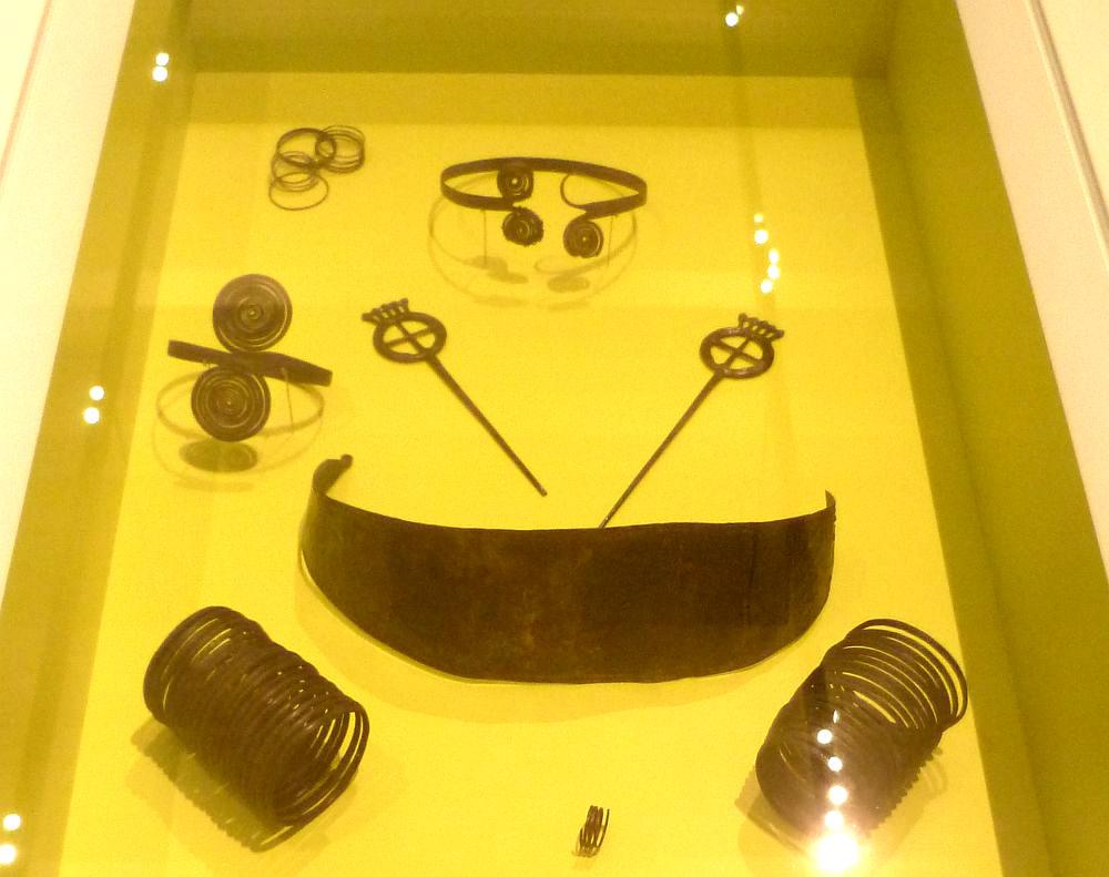 Die Grabausstattung der Frau von Molzbach. Es handelt sich um einen Halsring, zwei Radnadeln, Ein Grütelblech, Zwei Armspiralen, Eine Armberge, und einen Haarschuck aus Draht. Die Fundstücke liegen in einer gelben Vitrine.