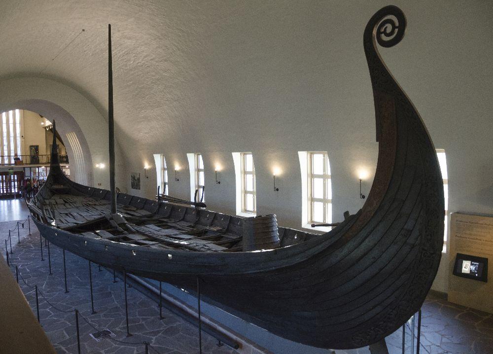 Das Osebergschiff so wie es heute Im Museum Steht. Es bsteht aus planken, und hat einen hoch gezogenen Bug, der in einem Kringel endet.