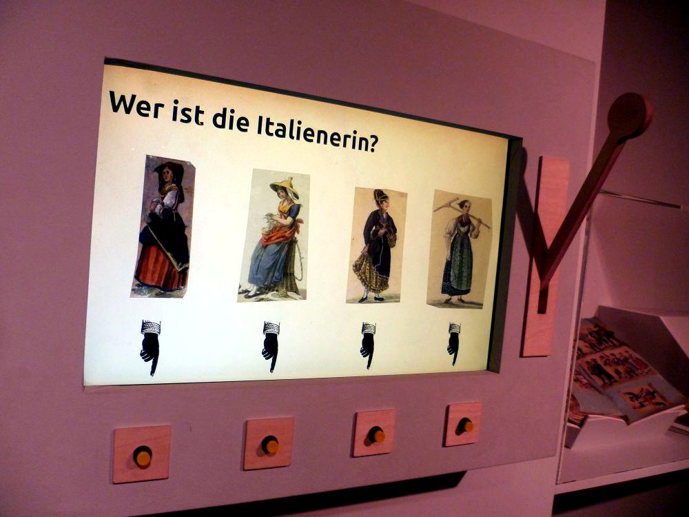 Eine Slotmaschiene. vier Fraun in Trachten werden gezeigt. Dadrübr steht die Frage: Wer ist Italienerin?
