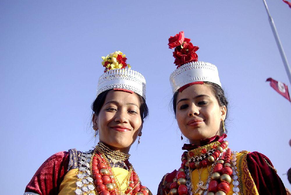 Zwei Khasi Mädchen. Sie Tragen silberne Kronen mit gelben und Roten Federbüschen oben drauf. Ihre Kleidung besteht aus gelben und roten Farben, sie ist allerdings kaum zu sehen, da die Mädchen Massiv Ketten tragen, die ebenfalls Silbern gelb und rot sind
