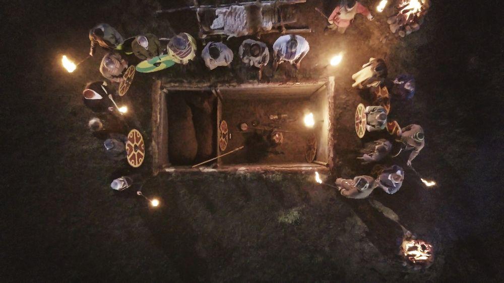 Bild auf eine Bestattung aus der Fotoperspektive. Viele Menschen Mit schilden tummeln sich um in große Grabkammer.