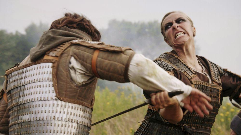 Ein Bild von einer Wikingerkriegerin die einen Schwertkampf durchführt. Sie trägt eine Rüstung, und ist in Aktion zu sehen.